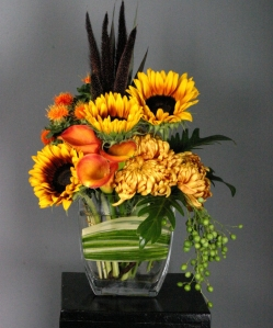 Sunflowers, Safflower, Millett, Mums, and China Berry are in abundance in this beautiful Autumn floral.