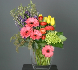 Peoples Collection: Gerbera Daisies arrangement displays the brilliant colors of the season. It features, Gerbera daisies, Larkspur and Tulips.